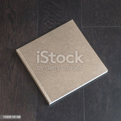 887572514istockphoto Blank square size book catalog magazine brochure note cover template, recycle brown paper texture, dark wood table desk background 1033516158
