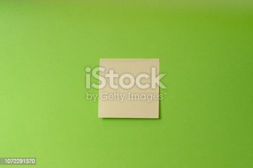 istock Blank stick note on green background 1072291370