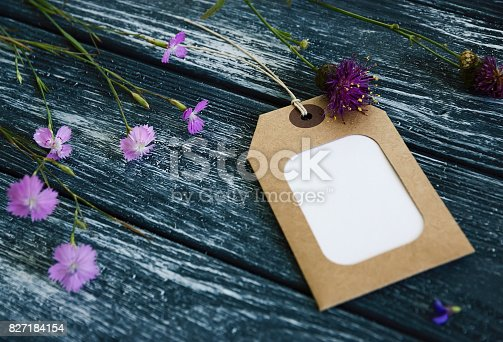 istock Blank sticker and wild carnation flowers Lie on  wooden table 827184154