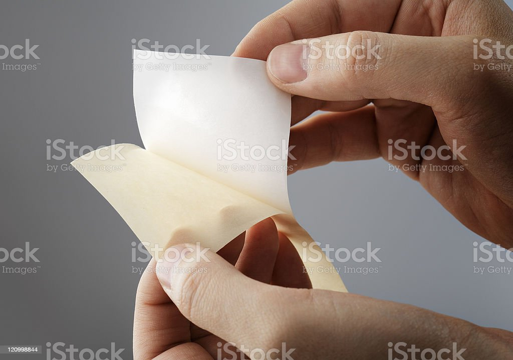 Blank sticker being separated from waxy backing stock photo