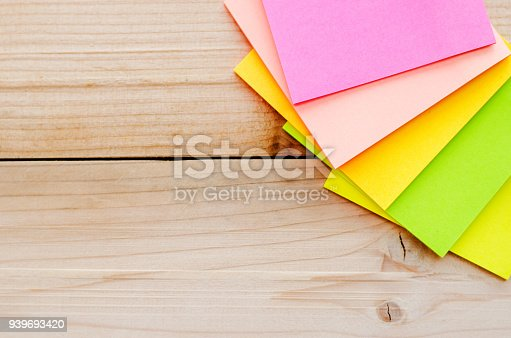 istock blank sticky note or post note colorful green yellow and pink on wood table or wood board. 939693420
