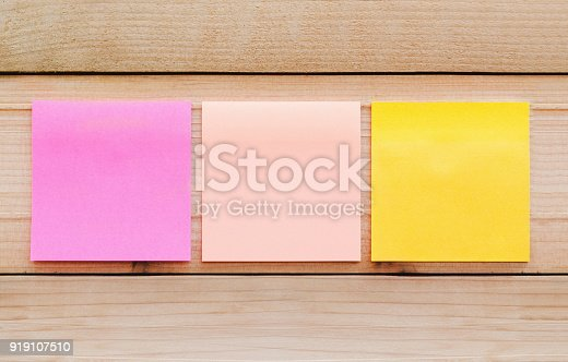 istock blank sticky note or post note colorful yellow and pink on wood table or wood board. 919107510