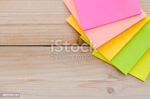 istock blank sticky note or post note on wood table or wood board. 892255134
