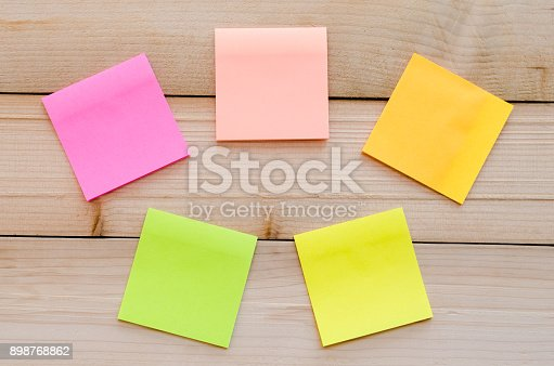 istock blank sticky note or post note on wood table or wood board. 898768862
