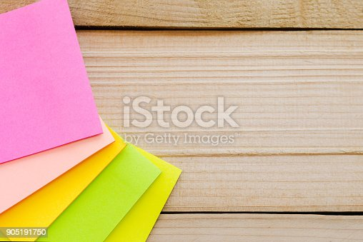 istock blank sticky note or post note on wood table or wood board. 905191750
