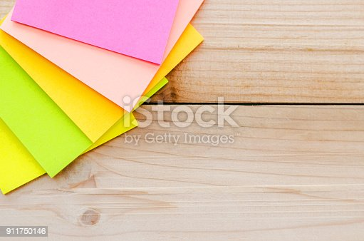 istock blank sticky note or post note on wood table or wood board. 911750146