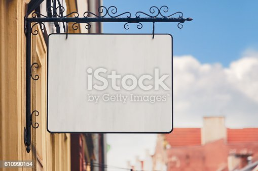 Blank old-fashioned restaurant/store sign on a city facade.