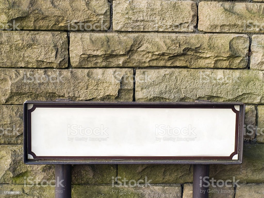 Blank street name sign against stone wall. stock photo