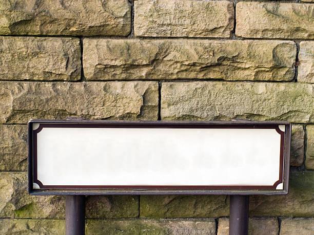leere straßenschild vor steinmauer. - straßenschild stock-fotos und bilder