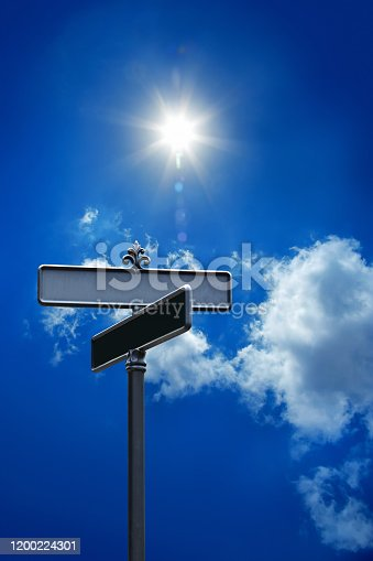 close up blank street name signs over clear blue sky with shinning sun