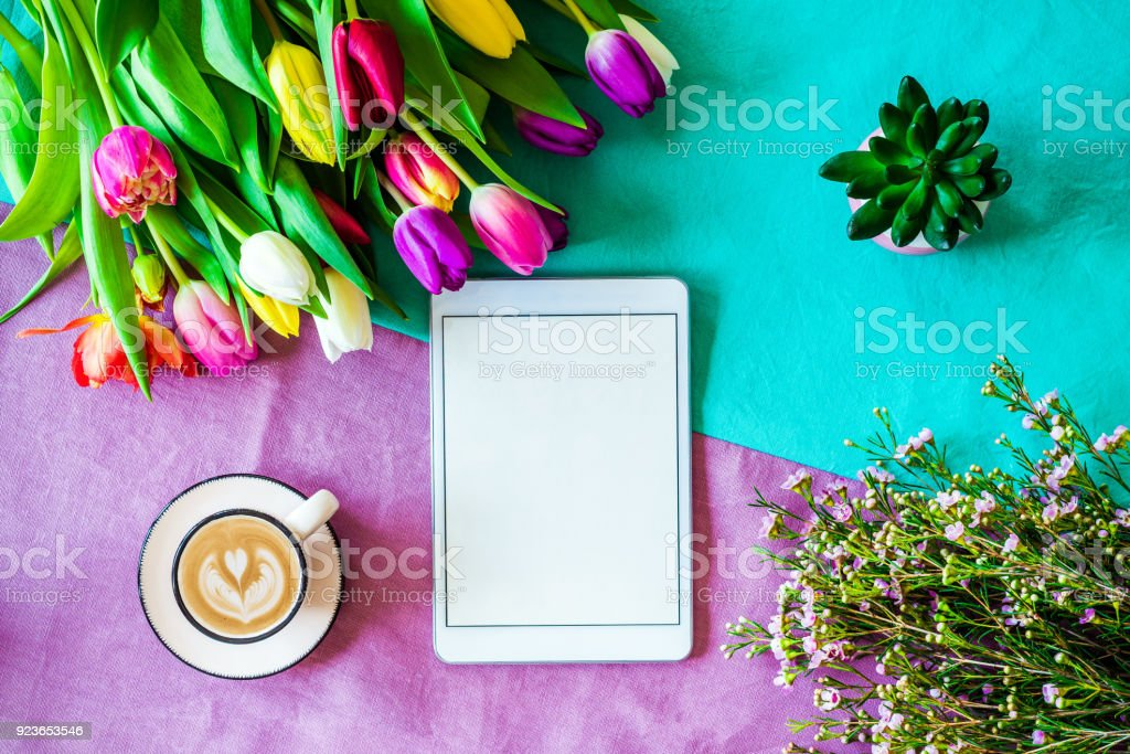 Blank tablet screen with free copyspace and easter and spring decorations from above stock photo