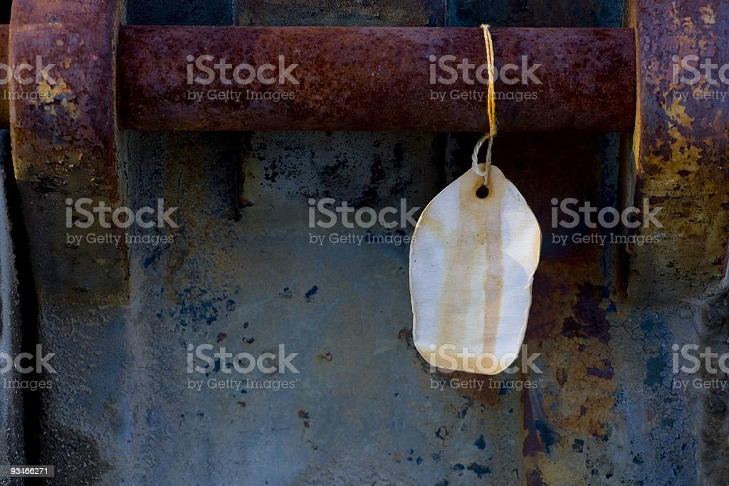 Blank tag hanging from rusty iron handle royalty-free stock photo