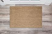 ホールの白いドアの前に空白の日焼け着色されたココナッツ玄関マット。製品のモックアップの木製の床をマットします。