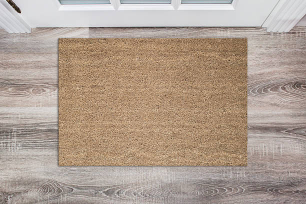 Blank tan colored coir doormat before the white door in the hall. Mat on wooden floor, product Mockup stock photo