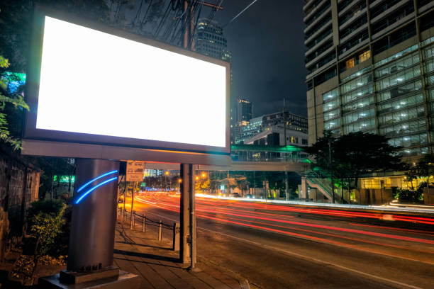 Blank template for outdoor advertising or blank billboard with light trail to business district in twilight.