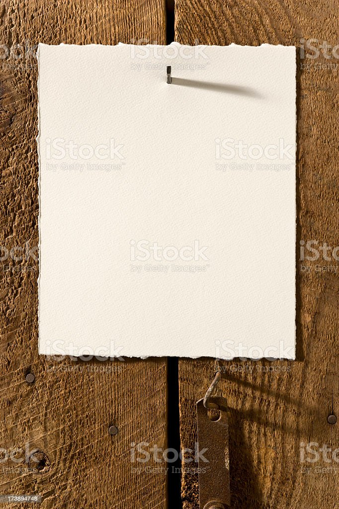 Blank Textured Paper Nailed to Old Weathered Wood. Vertical royalty-free stock photo