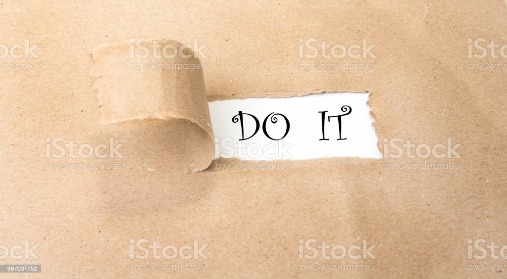 Blank torn brown paper revealing new challenges. Do it . stock photo