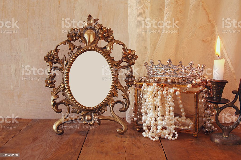 blank vintage frame, pearls on wooden table stock photo