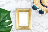 istock Blank Vintage golden color picture frame on green monstera leaf with sunglasses and straw hat on white marble table top view,Mock up for adding your photo in copy space,Summer vacation 809869564