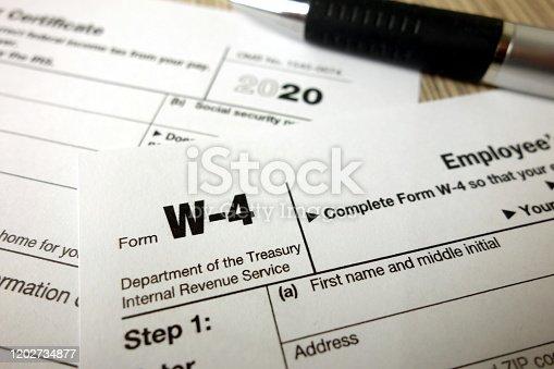 Blank W-4 form and a pen. Tax season