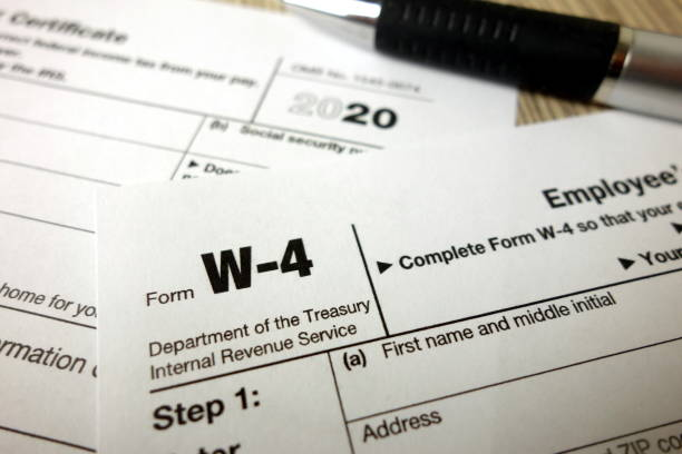 Blank W-4 form and a pen. Tax season stock photo