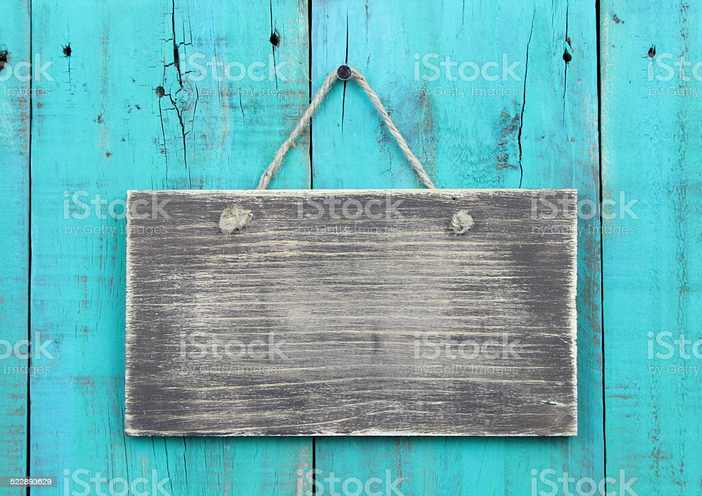 Blank weathered sign hanging on antique teal blue wood background stock photo