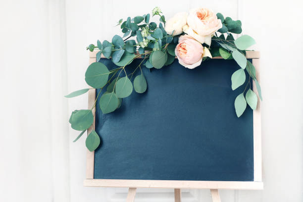 Blank wedding chalkboard sign mockup scene. Floral garland of green eucalyptus branches and apricot English roses flowers. Rustic birthday party decoration. Wooden easel with welcome board. stock photo
