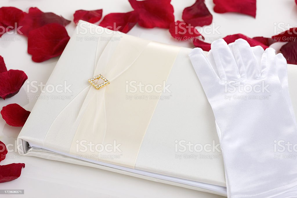 Blank Wedding Guest Book, White Gloves, and Red Rose Petals royalty-free stock photo