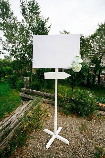 leere hochzeit weißen banner mit pfeil-zeichen dekoriert mit blumen - heiratssprüche stock-fotos und bilder