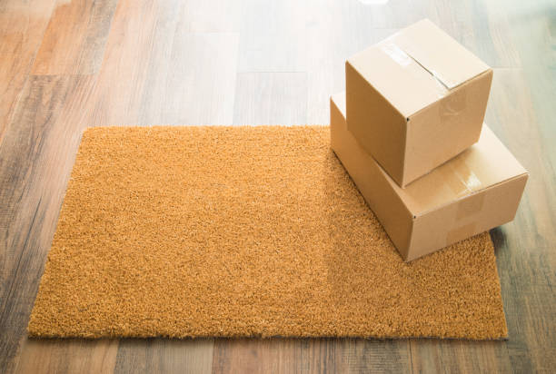 Blank Welcome Mat On Wood Floor With Shipment of Boxes stock photo