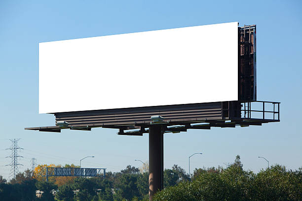 A blank white advertisement board on a motorway Blank billboard against blue sky, put your own text here billboard stock pictures, royalty-free photos & images