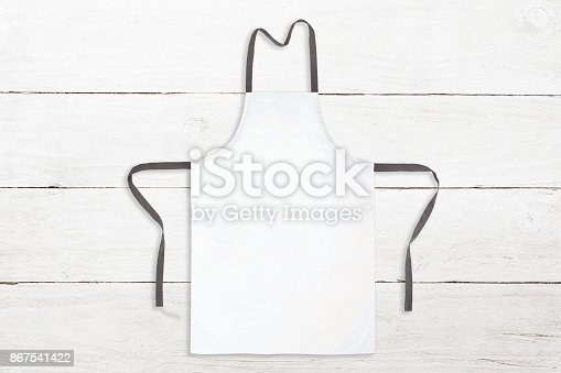 istock Blank white apron on wooden background 867541422