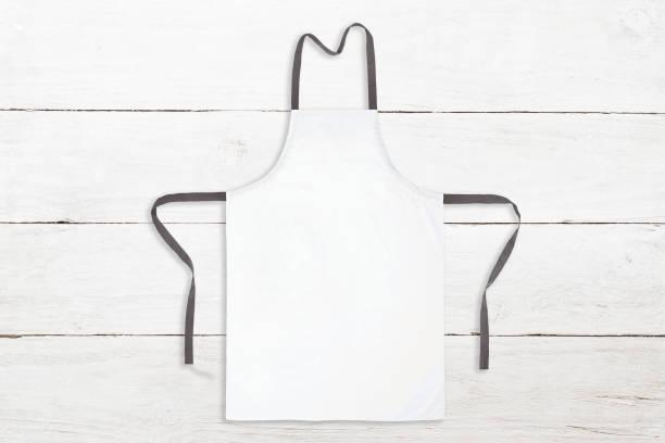 Blank white apron on wooden background stock photo