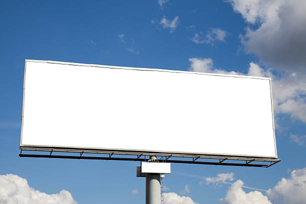 A blank white billboard against a blue cloudy sky stock photo