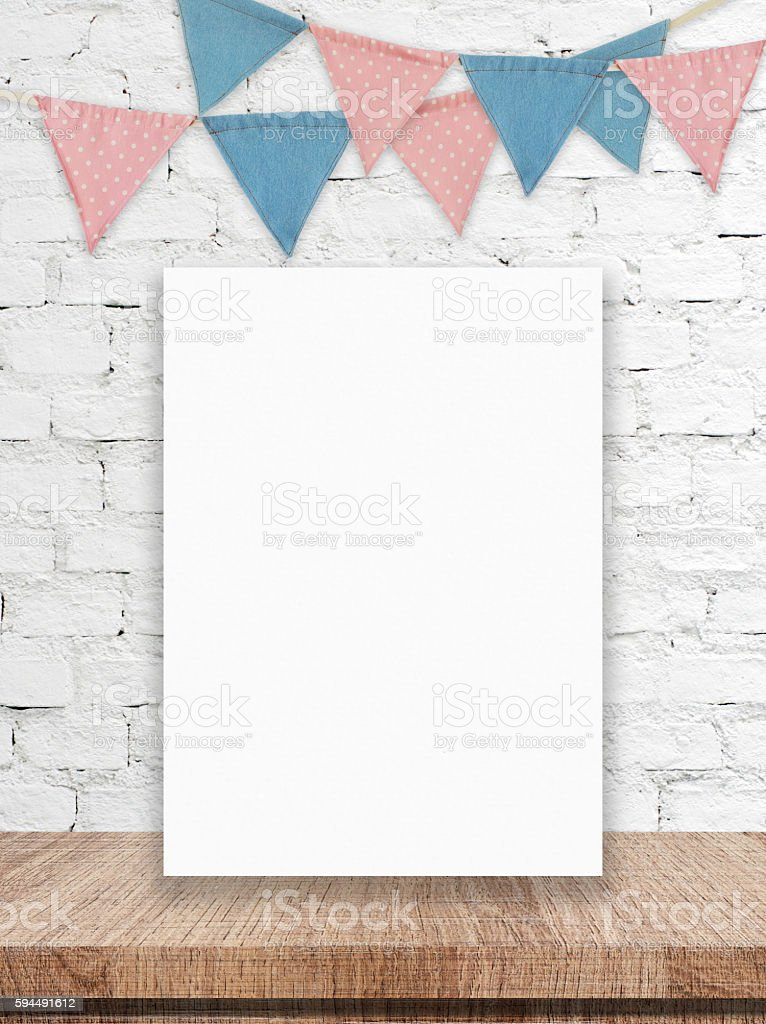 Blank white board and party flags hanging on brick wall stock photo