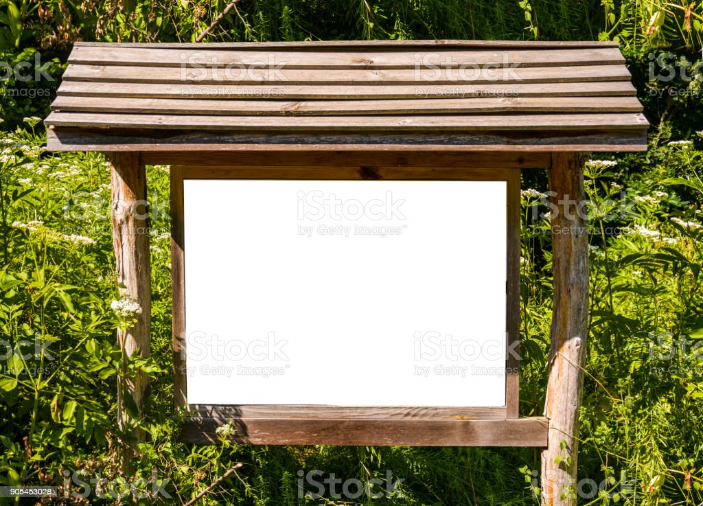 A blank white board in a forest for information stock photo
