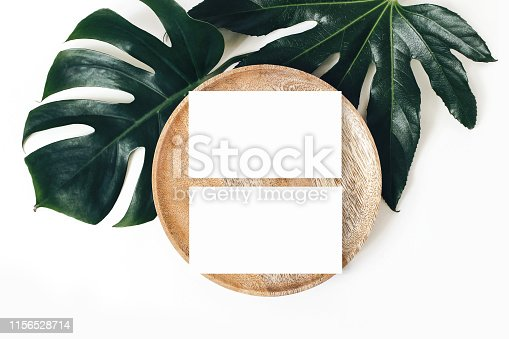 istock Blank white business cards mockups, wooden plate, aralia and monstera leaf isolated on white table backgound. Modern template for branding identity. Tropical design. Wedding stationery. Flat lay, top 1156528714