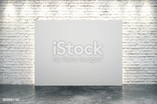 istock Blank white canvas in the center of white brick wall 503584762