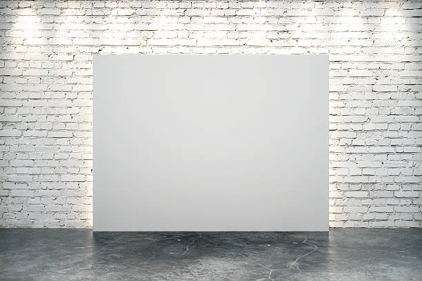 Blank white canvas in the center of white brick wall stock photo