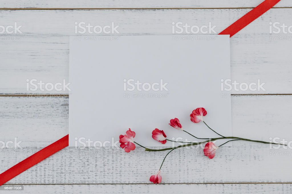 Blank white card decorate with red paper flowers and red ribbon royalty-free stock photo
