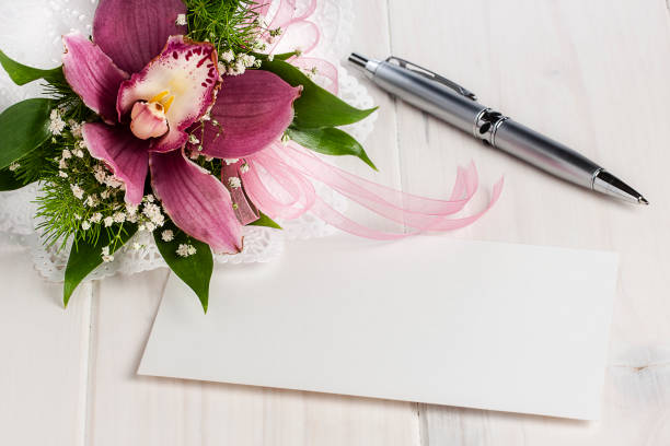 Blank white card on white wooden table next to orchid and silver ballpoint stock photo