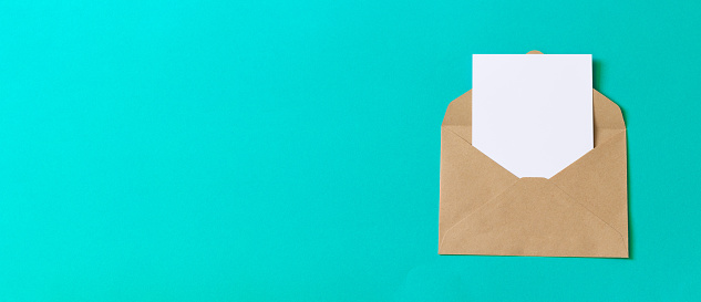 Empty blank white card with craft paper envelope template mock up on turquoise background. Flat lay, top view.