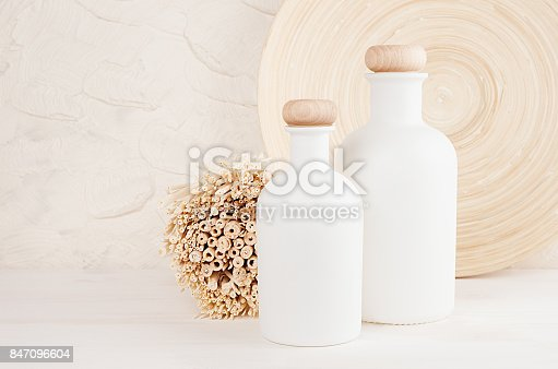 istock Blank white cosmetics bottles with comb, flowers on white wood board, mock up. 847096604