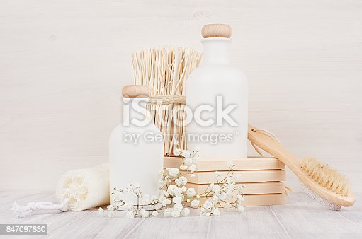 847096968 istock photo Blank white cosmetics bottles with comb, flowers on white wood board, mock up. Soft elegant bathroom decor for advertising, designers, branding identity, cover.