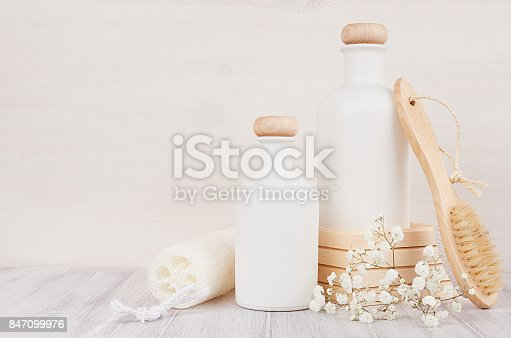 847096968 istock photo Blank white cosmetics bottles with comb, flowers on white wood board, mock up, copy space. 847099976