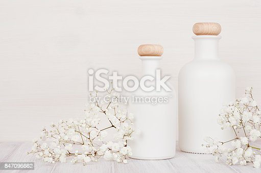 847096968 istock photo Blank white cosmetics bottles with small flowers on white wood board, mock up. 847096662