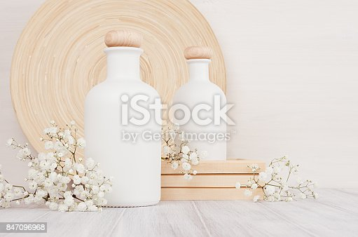 istock Blank white cosmetics bottles with small flowers on white wood board, copy space, mock up. 847096968