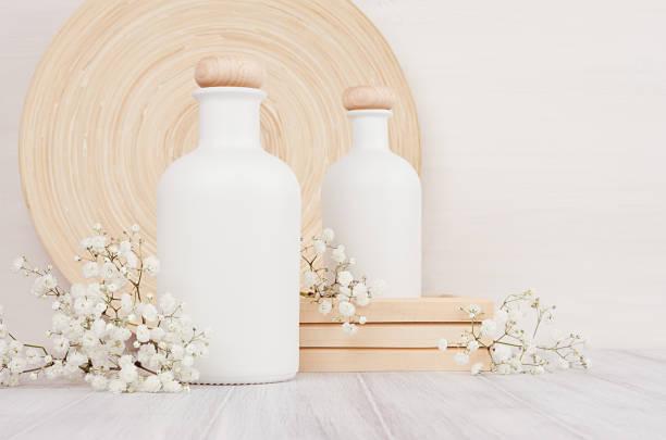 leere weiße kosmetikflaschen mit kleinen blüten auf weißem holz brett, textfreiraum, mock-up. - blumen make up stock-fotos und bilder