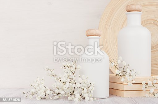 847096968 istock photo Blank white cosmetics bottles with small flowers on white wood board, copy space. Interior. Soft elegant home decor. 864371526