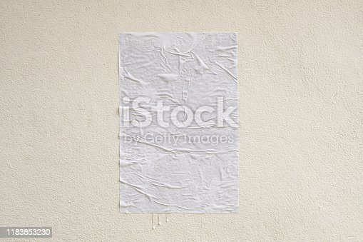 istock Blank white crumpled and creased adhesive street poster mockup on concrete wall background 1183853230